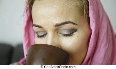 close-up of arabian woman in pink hijab drinks coffee.