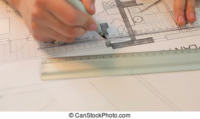Close up of architect hands working on blueprints