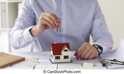 close up of architect with house keys at office -...
