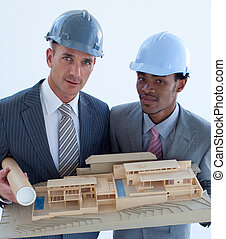 Close-up of architects holding a model house in office