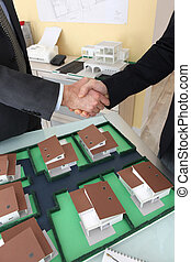 Close-up of architects shaking hands