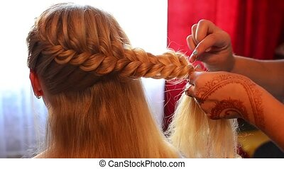 Close up of arms of hairstylist making pretty plait for a...