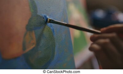 Close-up of artist woman's hand with brush painting still...