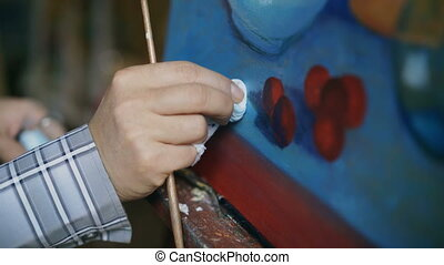 Close-up of artist's hand smearing oil paints on canvas...