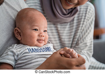 baby boy smiling while sitting on parent's lap