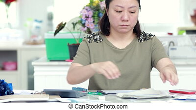 Close up of asian female accountant or banker making calculations. Home finances, investment, economy, saving money or insurance concept.