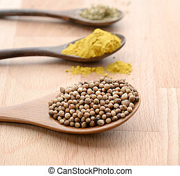 close up of assortment spices in wooden spoons on wooden background