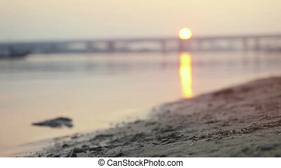 Close up of athletic man running on the beach at beautiful sunset in slowmotion.