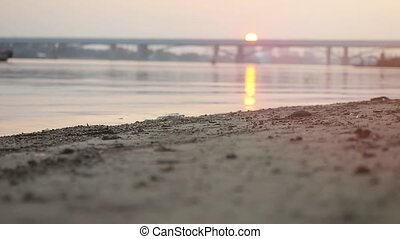 Close up of athletic man wear sneakers running on the beach at sunset in slowmotion on blurred bridge at background.