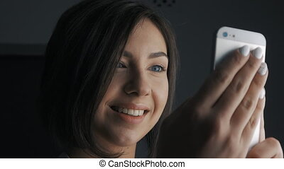 Close up of Attractive business woman smiling as she uses her touch screen phone