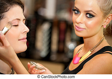 Close up of attractive female make up artist at work.