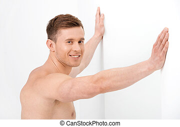 Close up of attractive nude guy resting both hands on a white wall. Standing shirtless isolated over white background