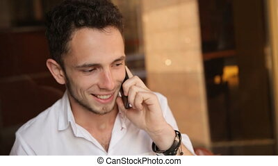 . Close-up of attractive young male in his 20s who actively speaking on cell phone
