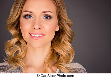 Close up of attractive young smiling woman on gray background