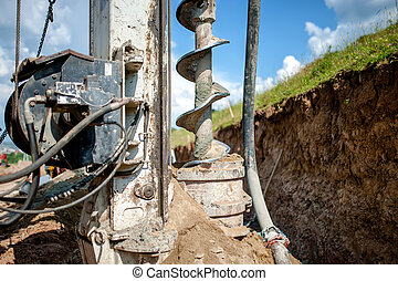 Close up of auger, industrial drilling rig making a hole in...