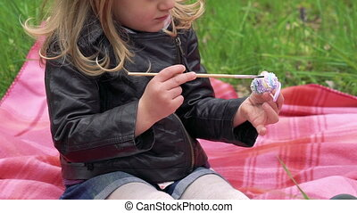 Close up of baby girl painting decorative egg for the Easter. Slowly