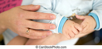 close up of baby in mother's hands