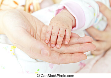 Close-up of baby's hand holding mother's hand