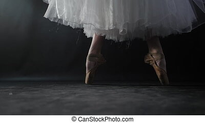 Close up of ballet dancer as she practices exercises on dark...