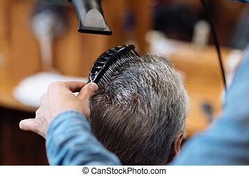 Close up of barber combing and blow drying