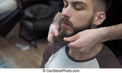Close-up of barber doing styling with a handsome man with a...