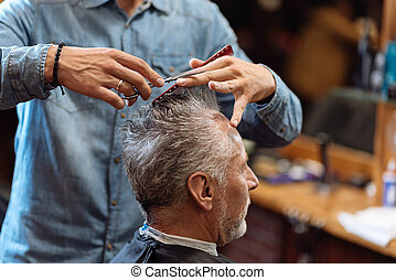 Close up of barber during haircut for grey-haired man