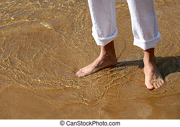 close-up of barefoot walking on the sand