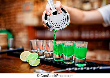 Close-up of bartender hand pouring alcoholic drink in...
