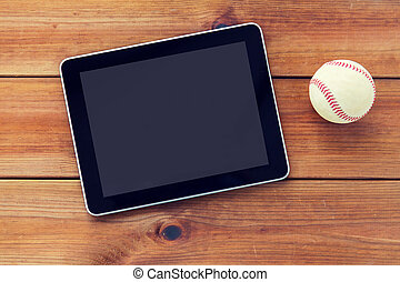 close up of baseball ball and tablet pc on wood