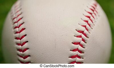Close up of baseball ball on green background