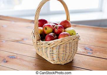 close up of basket with apples on wooden table