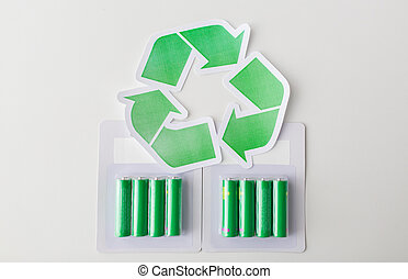 close up of batteries and green recycling symbol