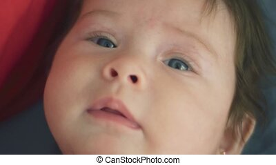 Close up shot in slow motion of baby looking at camera