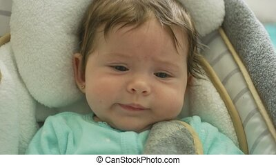 Slow motion close-up shot of a beautiful baby with blue eyes being tired