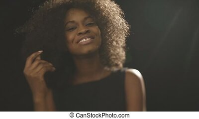 Close up of beautiful black woman cheerfully smiling on black background