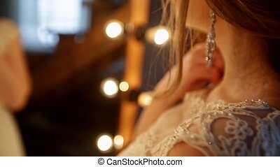 Close-up of beautiful bride stands in front of a mirror with lights in a loft interior