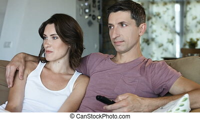 Close-up of beautiful couple relaxing watching tv at home on the couch with embrace