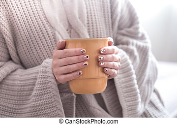 Close up of beautiful female hands holding big white cup of cappuccino coffee and flowers