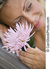 Close-up of beautiful flower by face of young woman