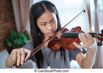 close up of beautiful girl playing violin with violin bow