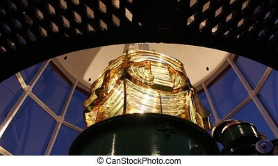 Close up of beautiful golden Fresnel lens inside Lighthouse,...