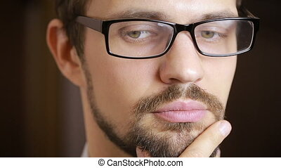 close-up of beautiful green-eyed man with a beard wearing glasses