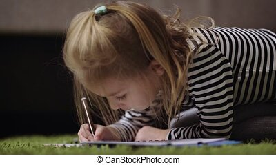 Close up of beautiful little girl in striped pullover drawing with brown pencil in nursery. Small princess is playing by painting the pattern with dark soft-tip pen. Cute child is spending her time at home relaxing and crayoning the picture on the floor with the bed in the background.