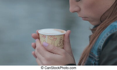 Close up of beautiful mysterious girl sitting by the sea with a cup of coffee