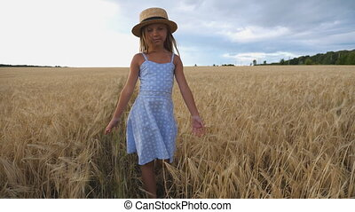 Close up of beautiful small girl with long blonde hair walking through wheat field. Cute child in straw hat touching golden ears of crop. Little kid in dress going over the meadow of barley. Dolly shot