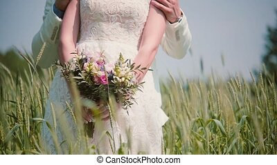 Close-up of beautiful wedding bouquet in hands of a bride standing with her groom in wheat field. Cones swaying in wind