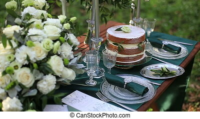 Close up of beautiful wedding table setting in rustic style in the forest