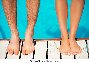 Close-up of beautiful woman and man legs near by swimming...