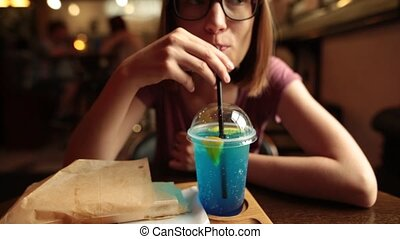 Close up of beautiful woman drinking ice blue lemonade in the cafe.