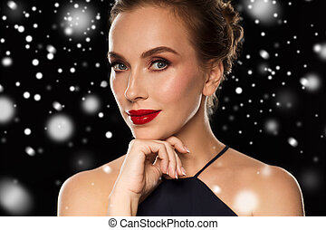 close up of beautiful woman in black over snow - people,...